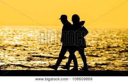 Couple walking sunset silhouette