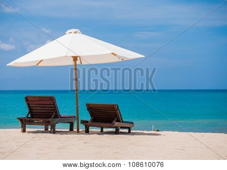 Beach chairs with umbrella and beautiful beach on a sunny day