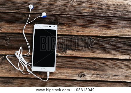 White Smartphone With Earphones On Wooden Table