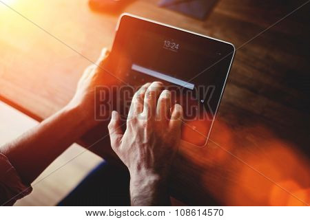 Young intelligent male working on touch pad while sitting at wooden table