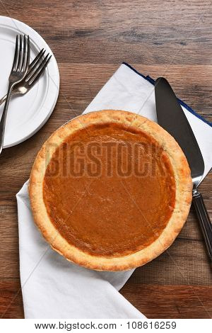 High angle vertical view of a pumpkin pie, server with plates and forks. The dessert is part of a typical Thanksgiving Day Feast.