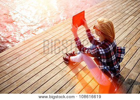 Young woman with trendy look shoot video on digital tablet while sitting on a wooden pier in summer