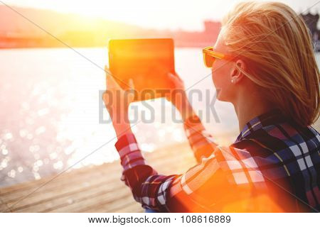 Young stylish hipster girl photographing on digital tablet beautiful sea landscape in summer evening