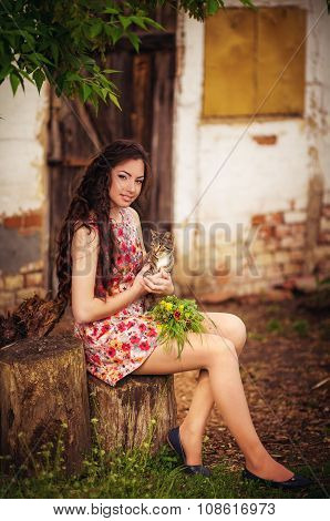 Beautiful young woman with cat in spring garden