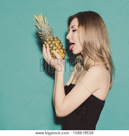 Girl Holding Hands Pineapple And Reaches For His Tongue In A Black Dress On A Green Background In Th