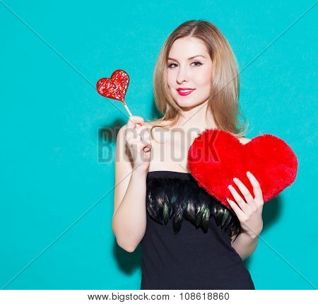 Fashionable Beautiful Girl Holding A Red Candy Heart And Big Toy Heart. In A Black Dress On A Green
