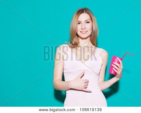 Young Woman Making A Call Me Sign And Smiling In Pink Dress With Glass In Her Hand. Green Background