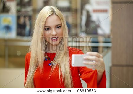 Young beautiful blonde girl taking selfie with mobile phone, in shop