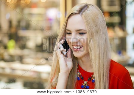 Young beautiful blonde woman in the red blouse talking on cell phone, indoor