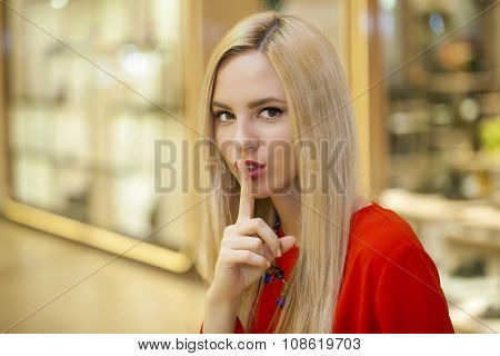 Portrait of attractive girl with finger on lips, concept of student show quiet, silence, secret gesture, young pretty blonde woman in reв dress