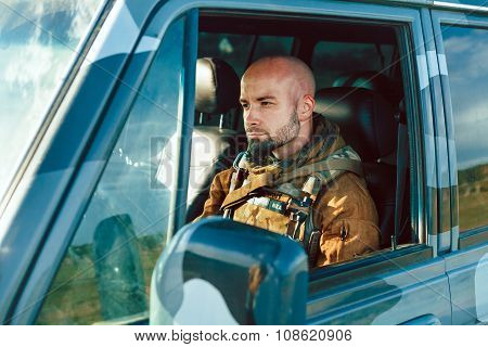 Bald Soldier In Uniform Is Driving Military Vehicle.