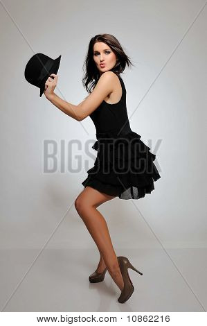 Sexy Beautiful Fashion Dancing Woman In Black Dress And Hat. Gray Background