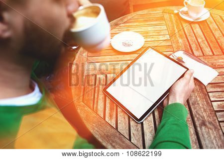 Young male reading electronic book while sitting in cafe