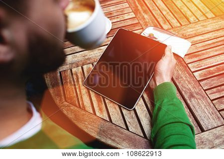 Rear view of young male freelancer drinking hot coffee and working on digital tablet in cafe outdoor