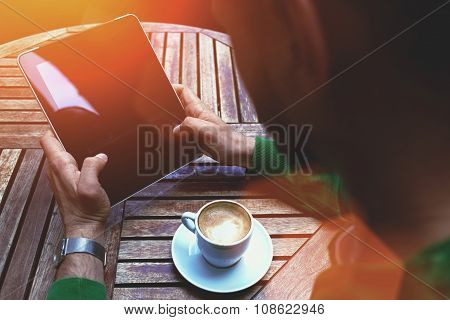 Male using digital tablet during coffee break in sidewalk cafe