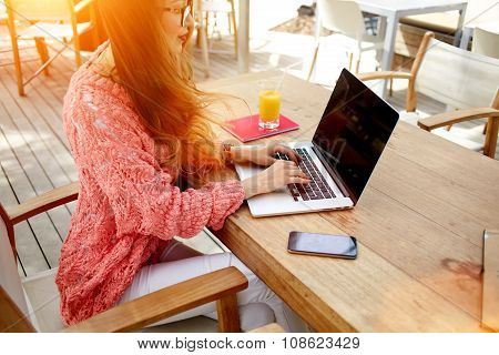 Young attractive woman working on net-book during morning breakfast in coffee shop