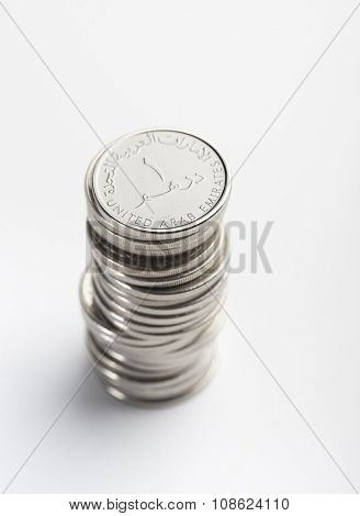Heap of UAE one dirham coins. Over the shoulder view.