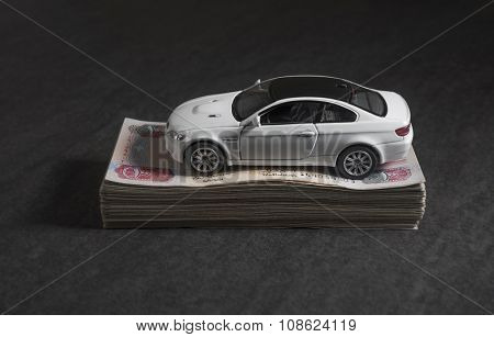 Dinky white car over the bundle of hundred dirham notes.