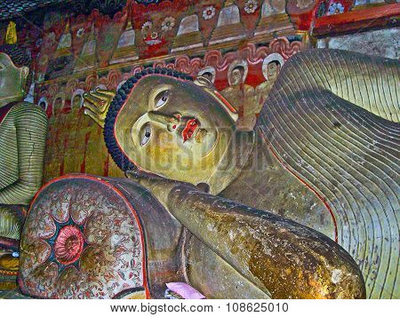 POLLONUARUWA, SRI LANKA - JUNE 4, 2011: Buddah and painting in the famous rock tempel of Dambullah Sri Lanka