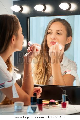 Pretty Young Woman Applying Lipstick