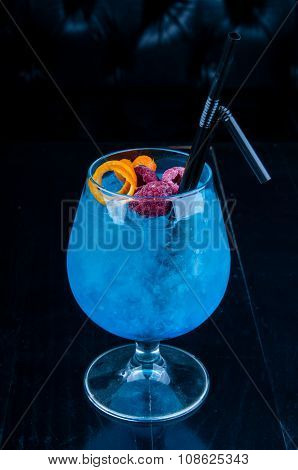 Blue cocktail served on a black table