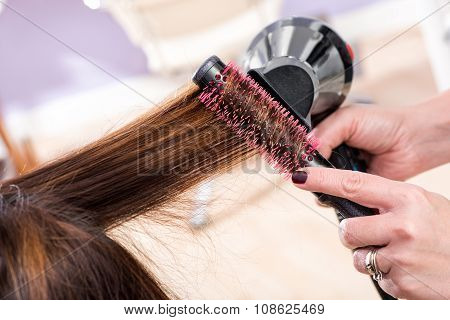 Hairstylist Brushing Hair With A Hairdryer