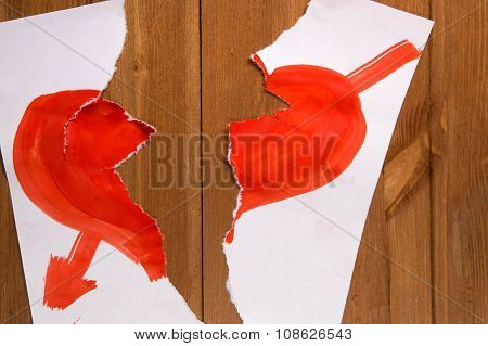 The Heart Drawn With Red Paint On A Sheet Of Paper And Which Is Broken Off In Half Lies On A Wooden