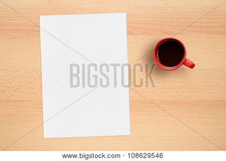 Blank Sheet Of Paper And Coffee Cup On Table