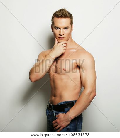 Sexy fashion portrait of a hot male model in stylish jeans with muscular body posing