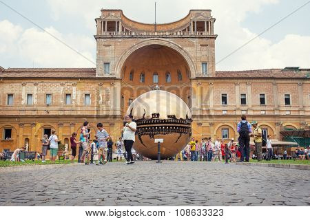 VATICAN - July 11, 2015: People around Sphere within sphere in Courtyard of the Pinecone at Vatican Museums. Sphere was created in 1990 by Italian sculptor Arnoldo Pomodoro