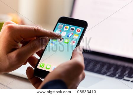 A man hand holding screen Apple app showing on iPhone 6 in office. Apple is the most valuable technology company in the World. PRAGUE, CZECH REPUBLIC - NOVEMBER 17,2015