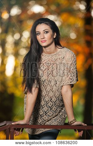 Beautiful woman in lace blouse posing in autumnal park. Young brunette woman spending time in forest