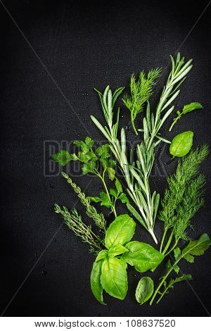 Fresh Aromatic Herbs With Water Drops On A Black Background , Top View
