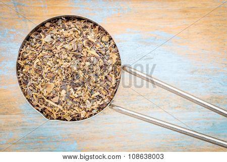 Irish moss seaweed - top view of a metal measuring scoop against painted wood