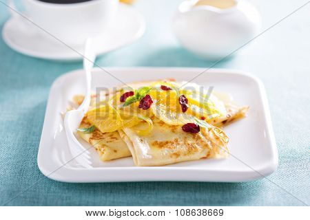 Thin crepes with citrus sauce and dried cranberry