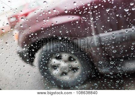 Wet Car Window With Raindrops And A Blurred Car
