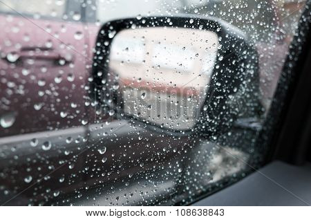 Wet Car Window With Raindrops And A Mirror Behind