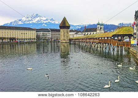 Cityscape of Lucerne with Chapel Bridge and Jesuit Church in Switzerland. Mount Pilatus overlooking Lucerne visible in the background