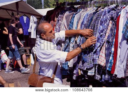 Man Choosing Shirt On Sale Of Outdoor Flea Market