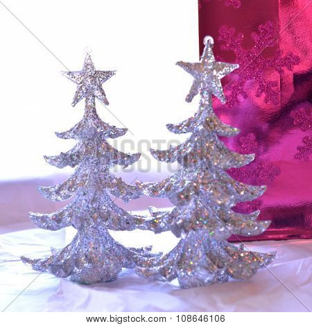 Two glittery Christmas trees, pink and white