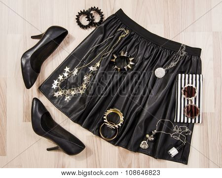 Black Leather Skirt And Accessories Arranged On The Floor.