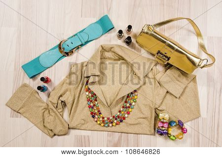 Gold Blouse And Accessories Arranged On The Floor.