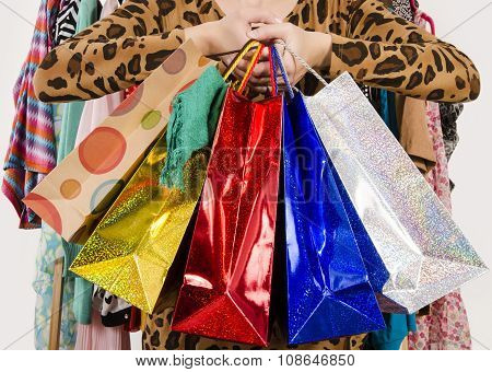 Close Up On Female Hands Holding Many Shopping Bags.