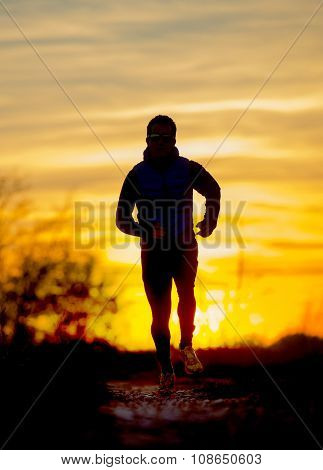 Silhouette Front View Of Young Sport Man Running Outdoors In Off Road Trail Track With Autumn Sun At