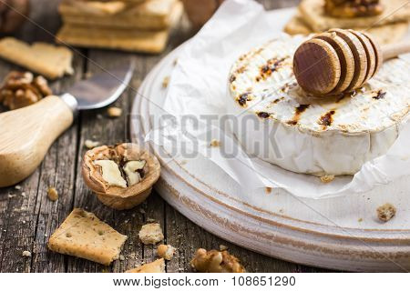Grilled Camembert Cheese With Crackers, Nuts And Honey