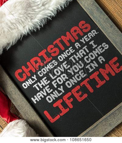 Inspirational Text About Love in Lifetime and Christmas written on blackboard with santa hat