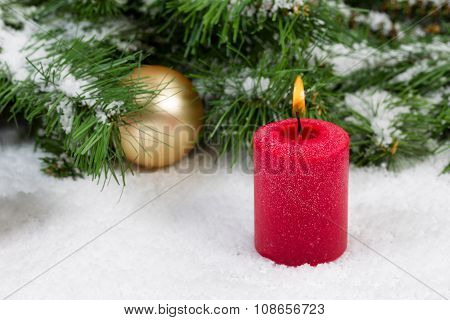 Burning Candle With Christmas Objects Covered With Fresh Snow