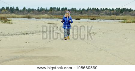 The Little Girl Goes On The Sandy Coast In Winter Clothes. Little Girl On A Sandy Autumn Beach.