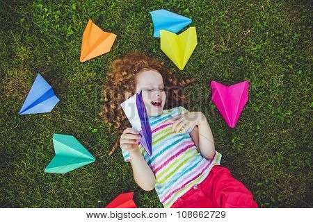 Happy Laughing Girl Throwing Paper Airplane In Green Grass At Summer Park.