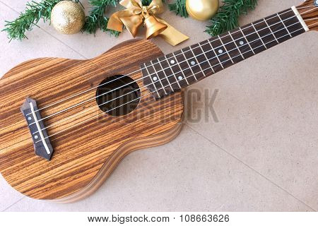 The Ukulele On The Wooden Table With Christmas Decoration